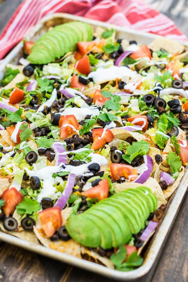 tray of seasoned black bean nachos with toppings