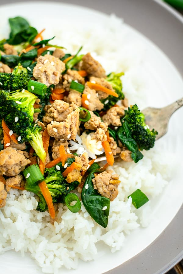 fork with a bite of ground pork stir fry with rice