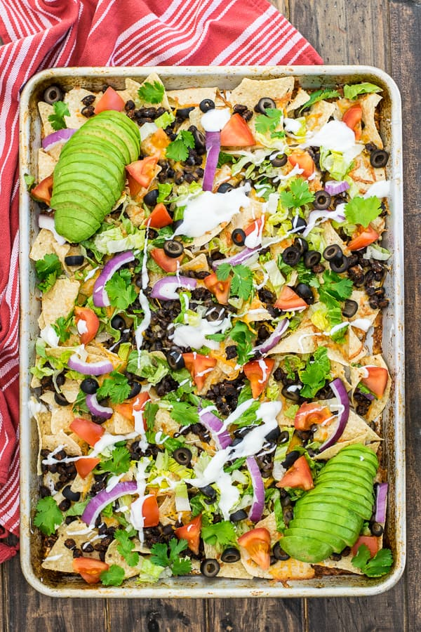 overhead shot of seasoned black bean nachos on a sheet pan