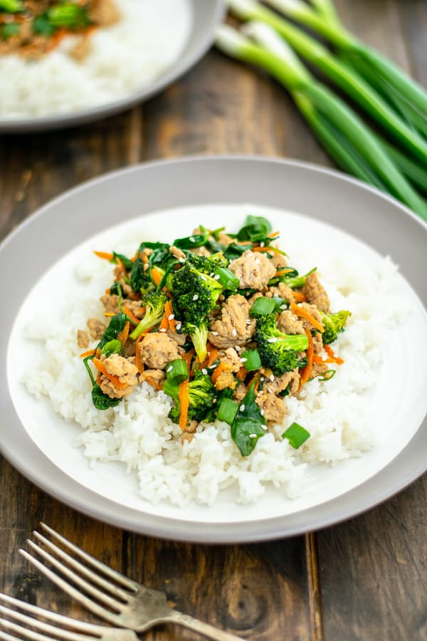 ground pork stir fry on a pile of rice on a white plate