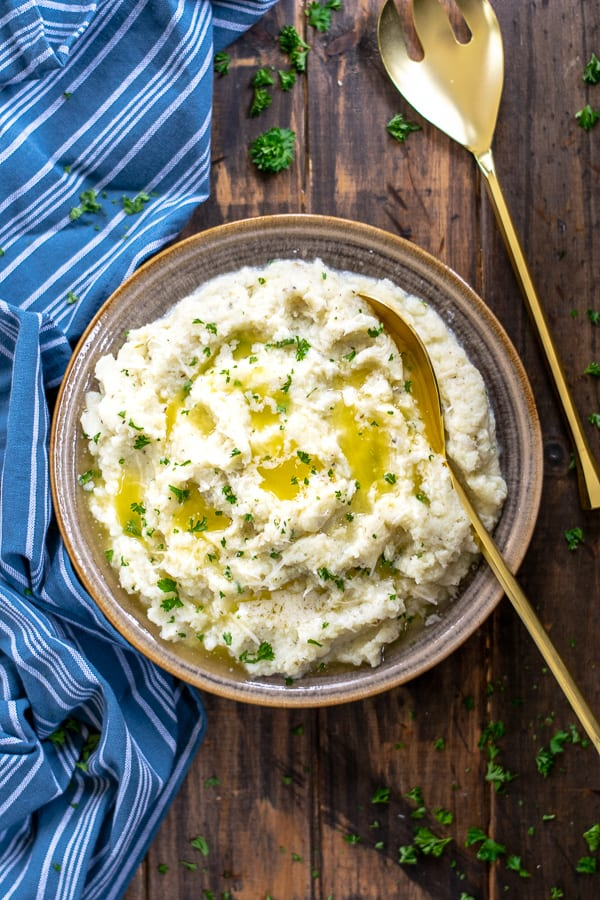 buttery cauliflower mash in a bowl with a gold spoon