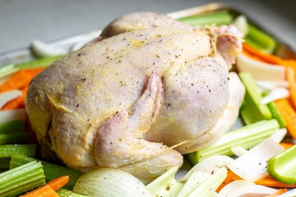 chicken trussed on a sheet pan over a bed of vegetables