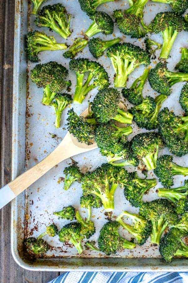 A wooden spoon scooping up oven roasted broccoli