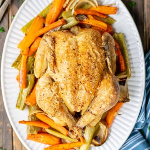 whole roasted chicken on a bed of veggies on a white platter