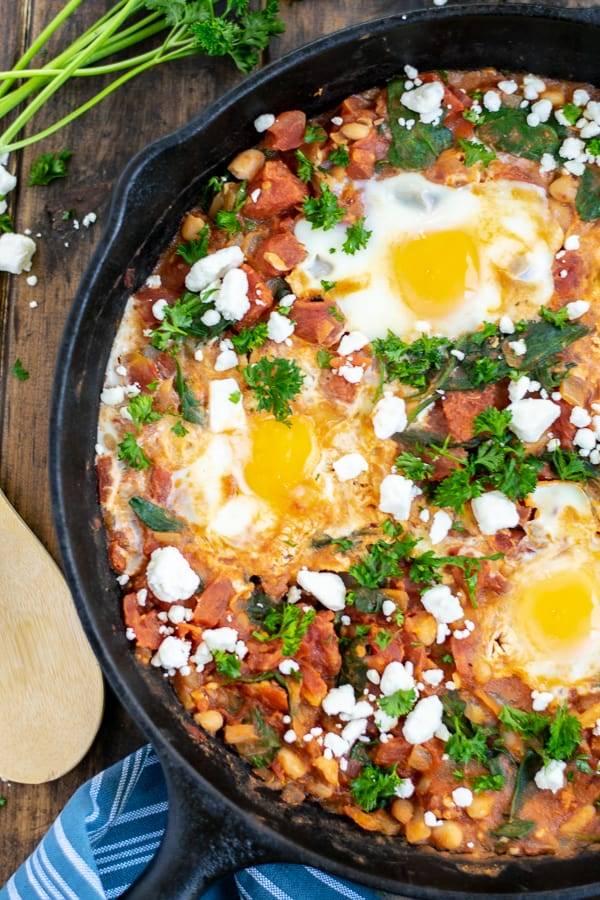 close up of cooked shakshuka with eggs in a cast iron skillet