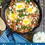 shakshuka with spinach in a cast iron skillet with a blue towel, feta, and parsley