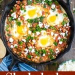 Overhead view of a shakshuka in a skillet on a table with parsley and feta