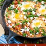 cast iron skillet holding a shakshuka with spinach and white beans