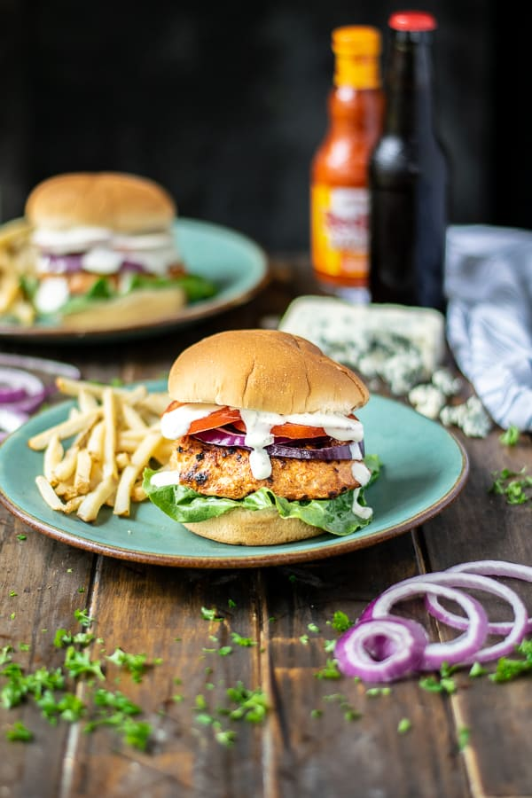 a stuffed chicken burger on a teal plate with French fries on a table