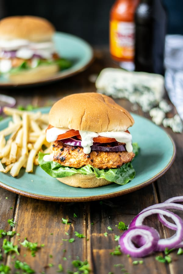 chicken burger stuffed with buffalo and blue cheese on a teal plate with French fries