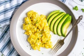 cottage cheese scrambled eggs and sliced avocado on a plate with a fork