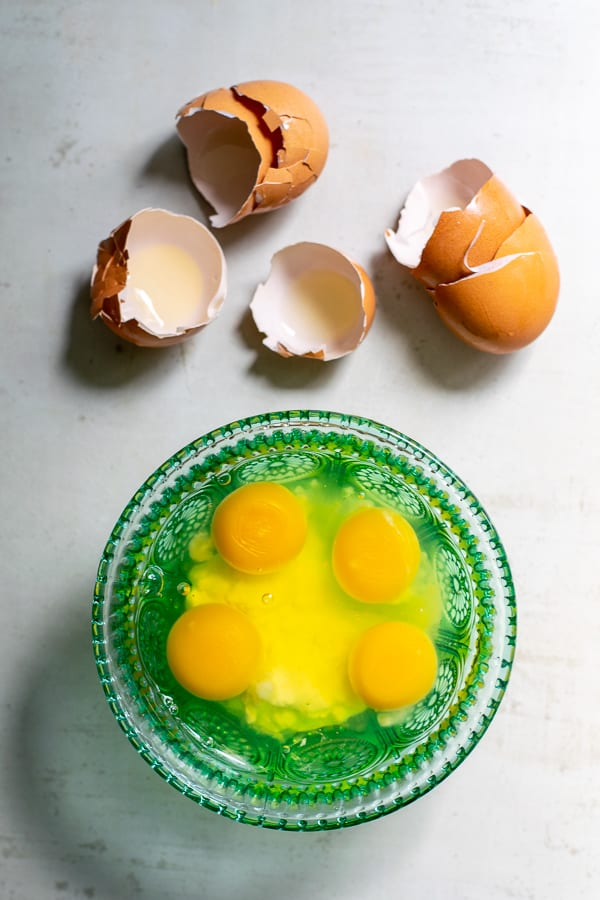 4 cracked eggs in a blue bowl with the brown shells sitting next to it