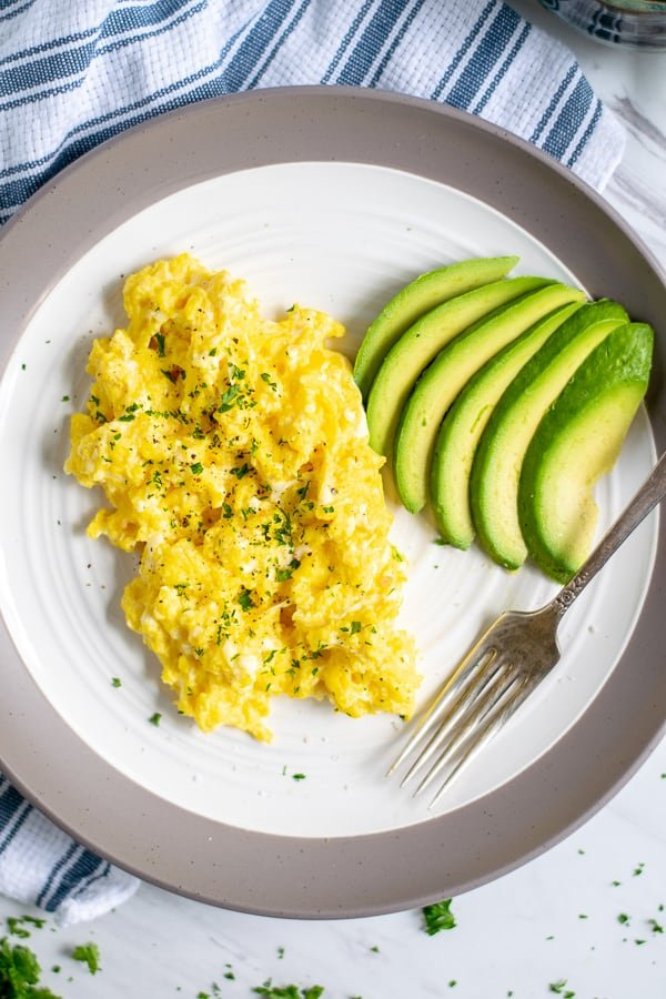 overhead shot of scrambled eggs on a plate with sliced avocados and a fork