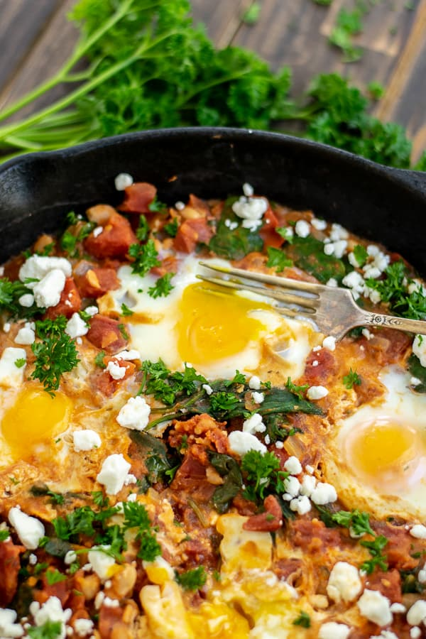 a fork in the runny yolk of an egg in the shakshuka
