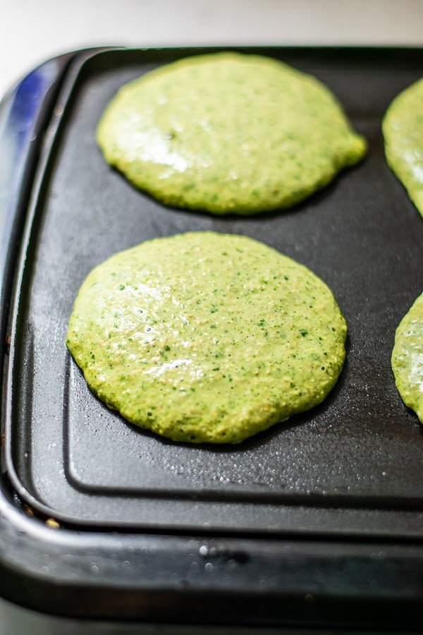 green pancakes being cooked on a black griddle
