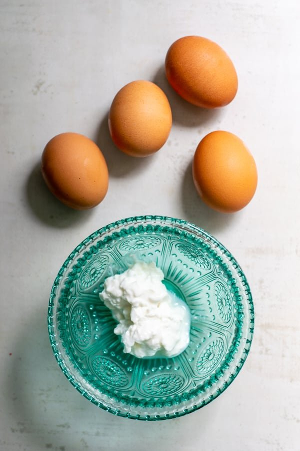 cottage cheese in a blue bowl with 4 brown eggs next to it on a counter