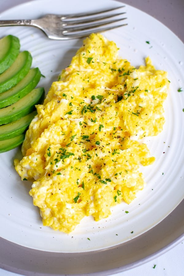 scrambled eggs with salt, pepper, and parsley on a white plate