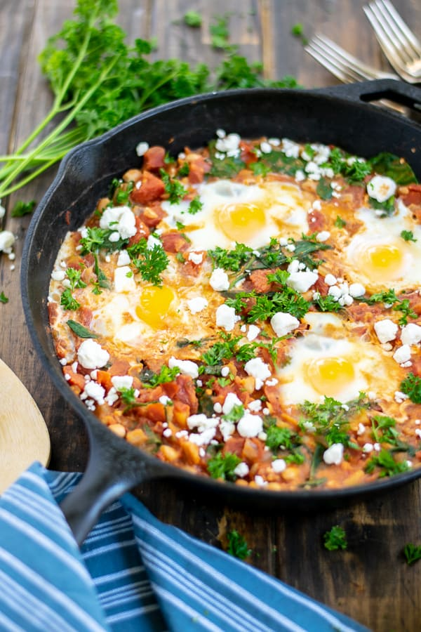 skillet of shakshuka with beans on a table with parsley and feta