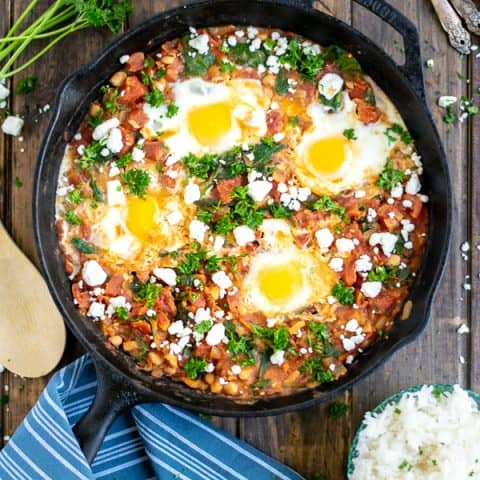 overhead shot of shakshuka in a cast iron skillet on a wood table with a blue striped towel
