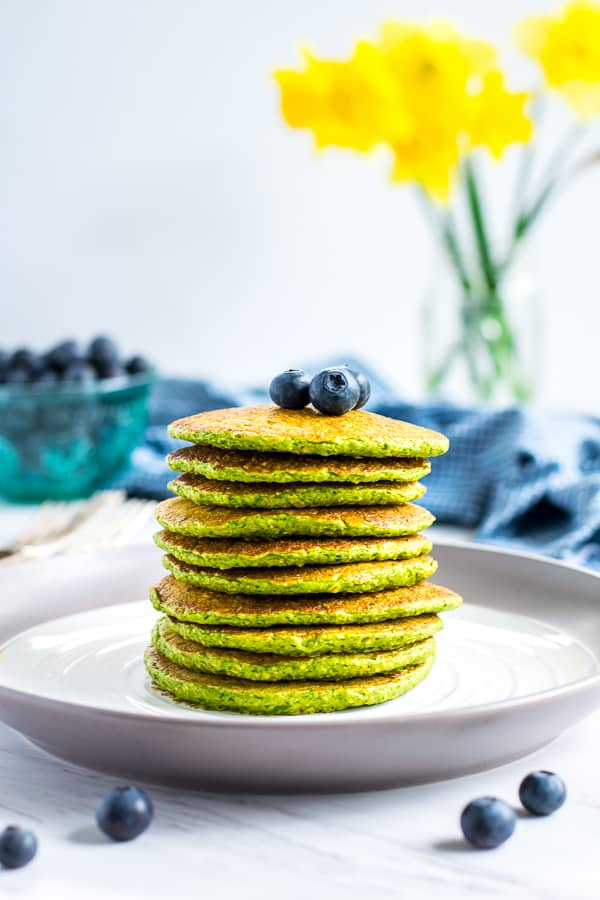stack of green spinach oatmeal pancakes on a white plate topped with blueberries