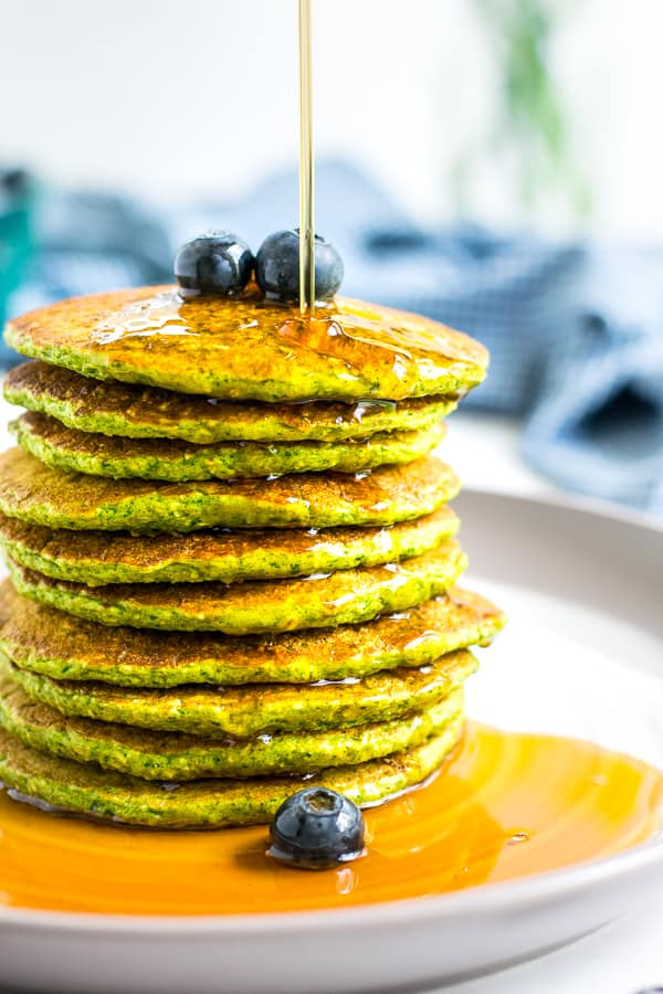 Stack of Spinach Pancakes on a plate with blueberries on top and syrup being drizzled over the top