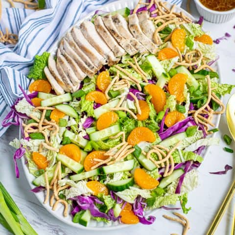 Asian Chopped Chicken Salad on a large plate on a tables with garnishes