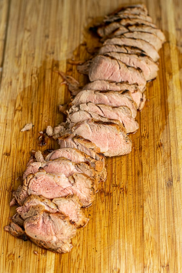 a pork tenderloin sliced open reveling a slightly pick center on a cutting board
