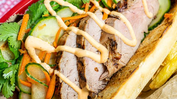 a flavorful grilled pork banh mi in a serving basket with quick pickled vegetables, sriracha mayo, and cilantro