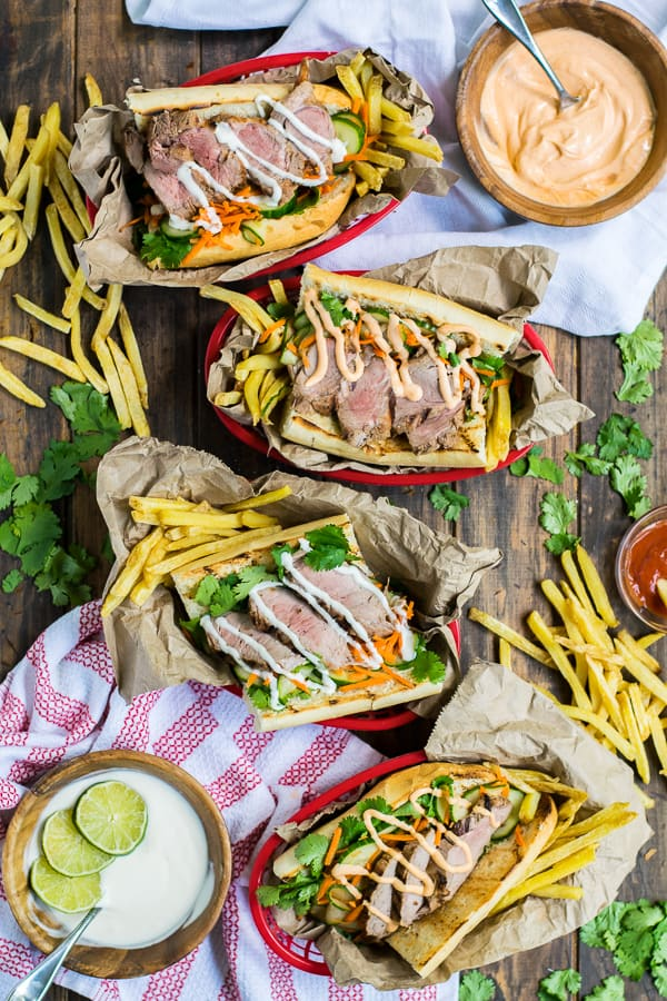 four serving baskets filled with fries and grilled pork banh mi's on a table top with flavorful mayo sitting in bowls