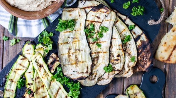 a spread of grilled zucchini, eggplant, naan, and hummus over a wooden background