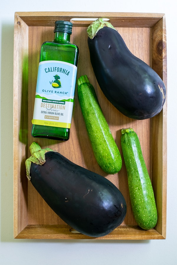 olive oil, zucchini, eggplant on a wooden tray