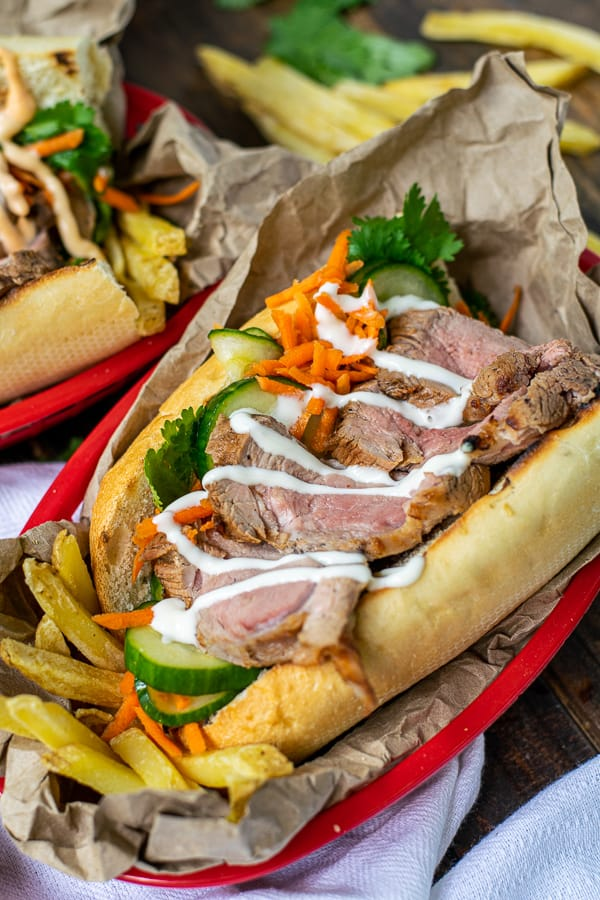 garlic lime mayo drizzled over a banh mi in a serving basket with French fries