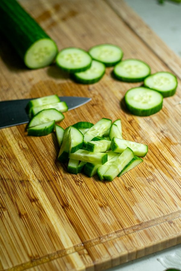cucumbers being cut up into matchsticks for the salad