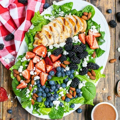 overhead view of a summer berry salad on a large platter with a napkin and a lot of berries