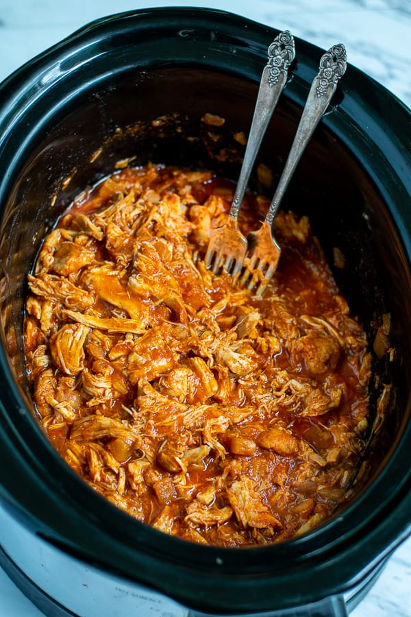 shredded bbq chicken in the crockpot with forks
