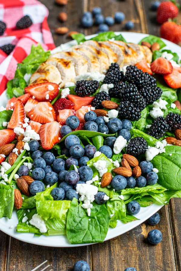 three different kinds of berries with grilled chicken on top of fresh salad greens with almonds and feta cheese on a large platter