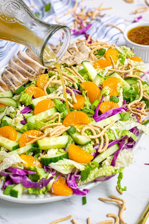 sesame vinaigrette being poured onto a plate full of asian chopped salad