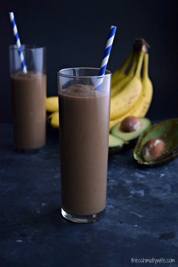 glass full of chocolate avocado smoothie with a blue straw