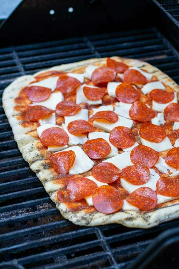a pepperoni pizza on the grill cooking