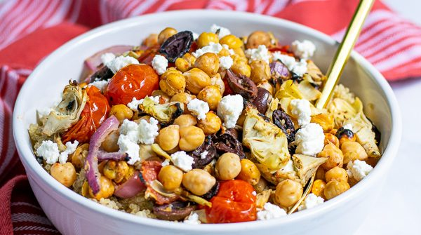 Healthy Chickpea Salad with Feta in a white bowl with a red napkin and gold spoon