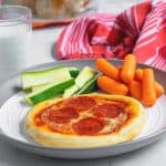 easy weeknight personal pizza on a white plate with vegetables is perfect for kids