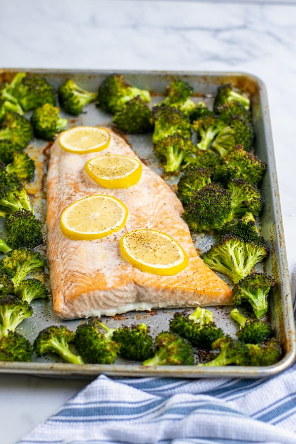 salom and broccoli just baked on a single sheet pan with lemons
