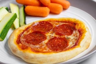 close up of individual pizza on a plate with vegetables perfect for a weeknight dinner