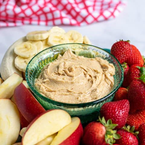 Platter with peanut butter fruit dip surrounded by cut up fruit.