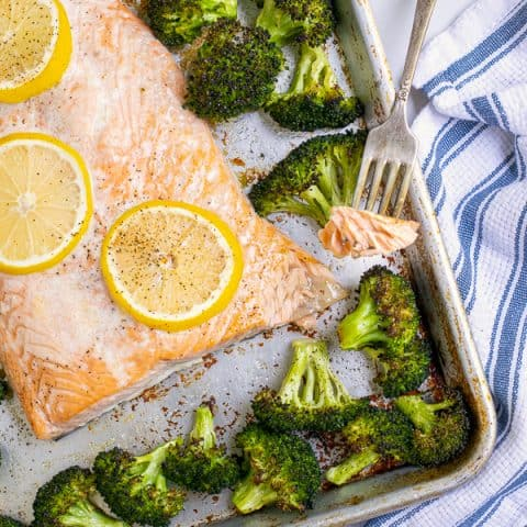 forkful of baked salon with broccoli on a sheet pan