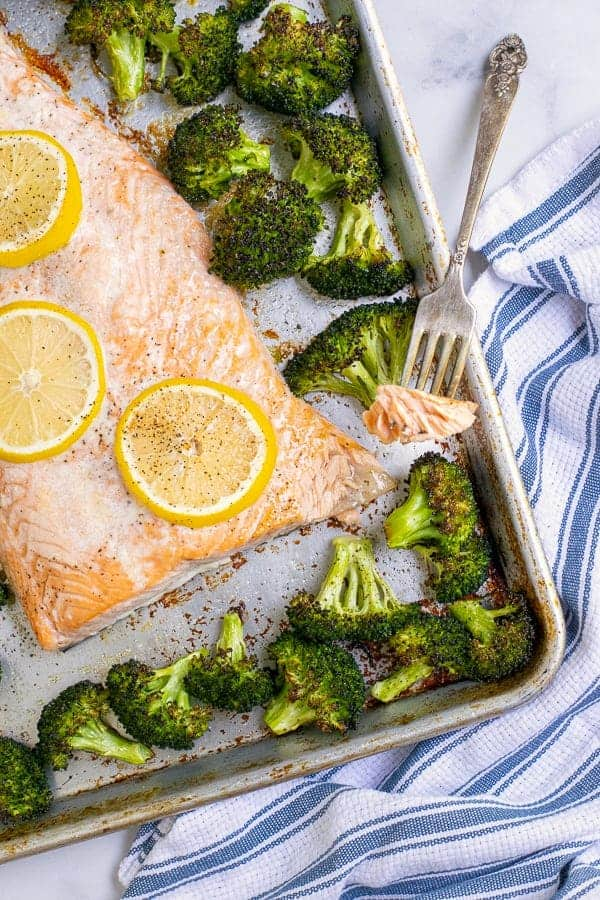 Forkful of baked salmon with broccoli on a sheet pan.