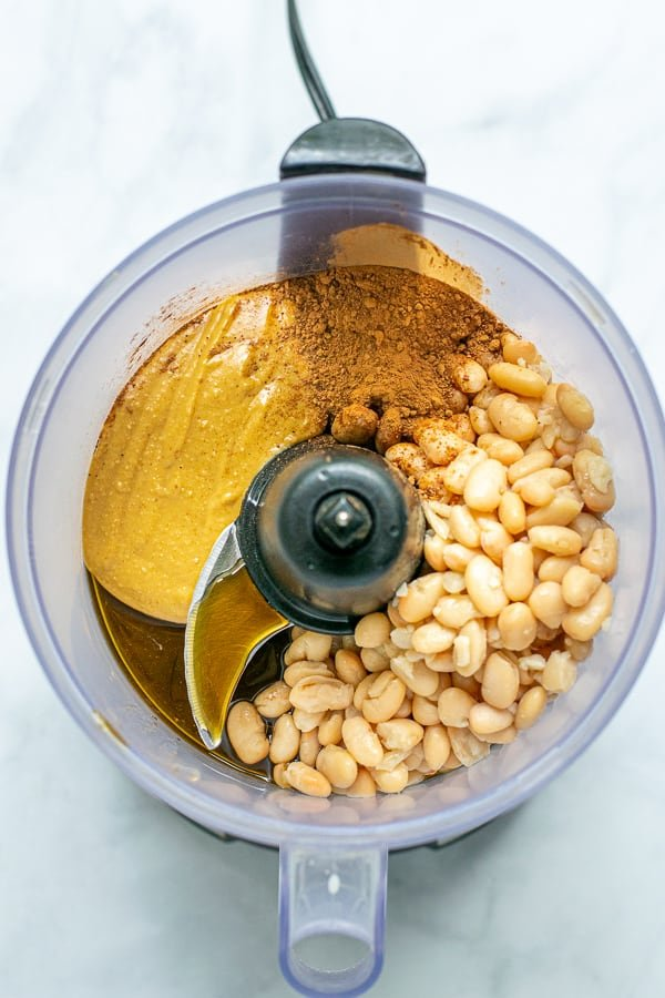 ingredients in a food processor ready to be blended into hummus