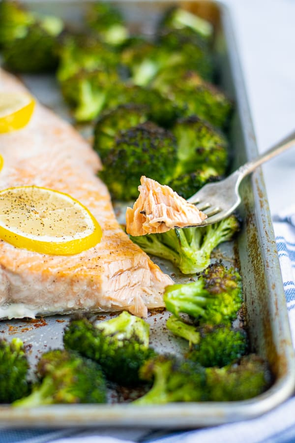 bite of cooked salmon on a fork resting on a sheet pan of salmon and broccoli