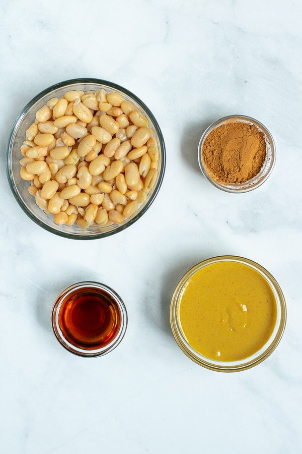 the four ingredients for chocolate hummus, great northern beans, cocoa powder, peanut butter, and maple syrup