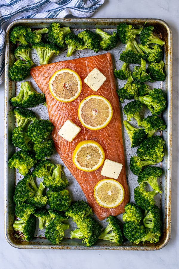 overhead view of raw broccoli and salmon on a sheet pan ready for the oven